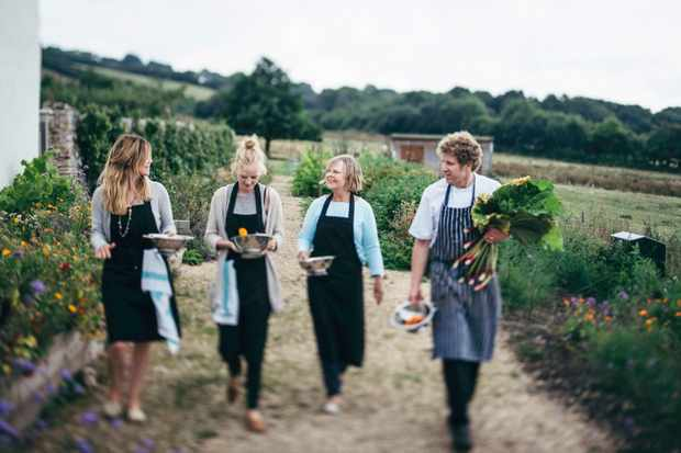 Three women and one man is walking through the River Cottage gardens with fresh produce in their hands. They are all wearing aprons
