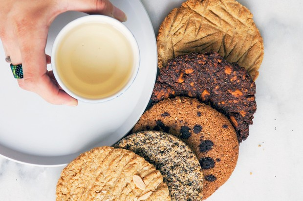 A hand is holding a cup of coffee and to the side of it are five cookies of assorted flavours