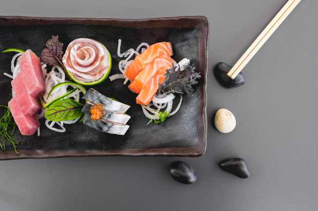 A rectangular black plate is topped with 9 pieces of sushi including salmon. They are vibrant orange and pink and a pair of chopsticks are at the side of the plate