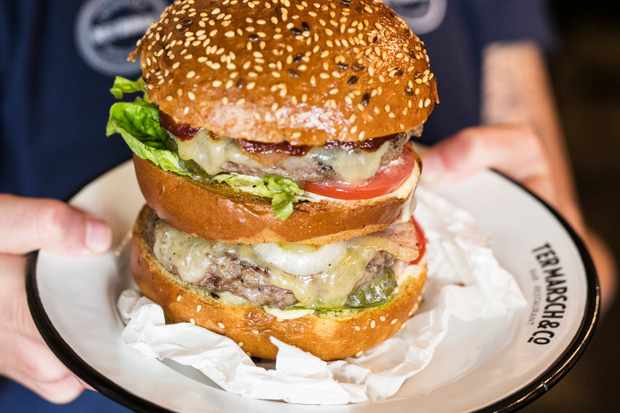 A person is holding a white plate and on the plate is a double decker burger with a sesame bun