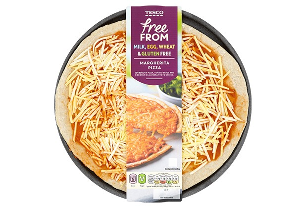 An uncooked pizza is topped with grated cheese and tomato sauce. There is a cardboard sleeve with Tesco free from written on it