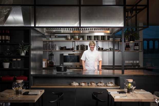 Chef Dale Mailley is stood in the kitchen in the kitchen of The Lookout restaurant. He is wearing chefs whites and is in the open-style kitchen surrounded by pans