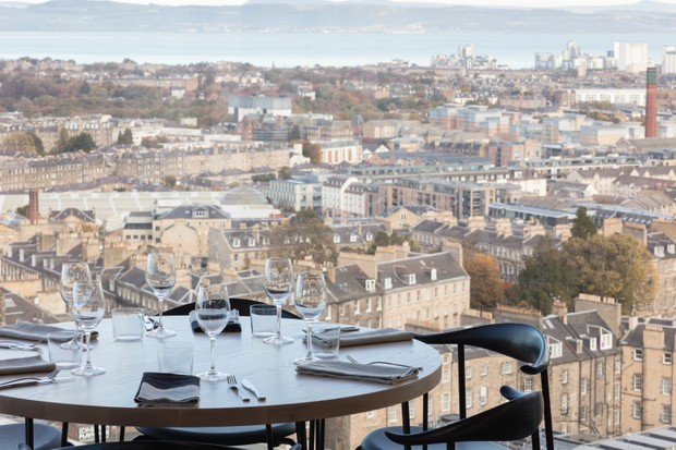 A round white table is next to the floor to ceiling windows with stunning views over Edinburgh city centre