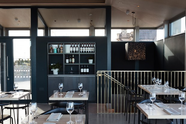 Wooden tables for two and simply laid with wine glasses and linen napkins. The walls are painted a very dark grey and there is a cabinet filled with bottles of wine. There is a gold railed staircase is the in the image too