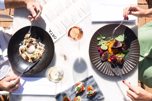 An overhead shot of two black plates with people holding knives and forks over the plates. They each have a glass of wine and menus on the table