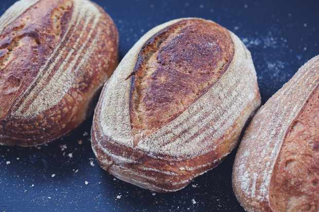 Three loaves of sourdough bread on a dark background