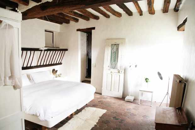 A bedroom has white washed walls and exposed beams on the ceiling. There is a double bed with white linen and a simple cream rug on a stone floor