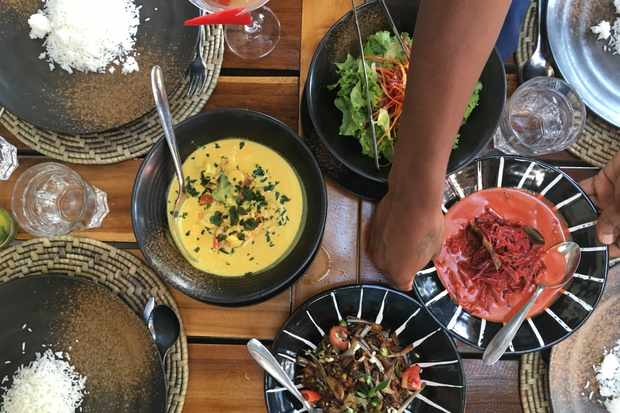 A wooden table is laid with colourful dishes from the cooking class including a prawn curry