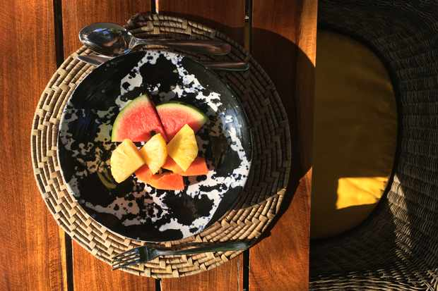 A sun dappled table is topped with a speckled bowl. In the bowl is chunks of pineapple and watermelon