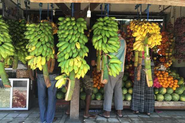 A fruit market has rows of green and yellow bananas hanging outside
