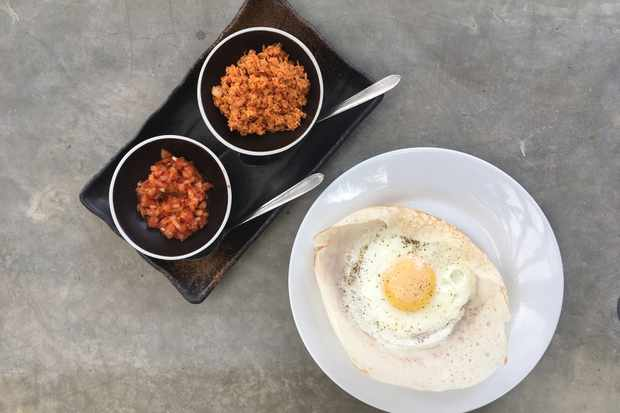 A grey table is topped with a white plate. On top of the plate is a hopper with a fried egg. To the side there are two pots filled with chilli-spiked coconut sambol