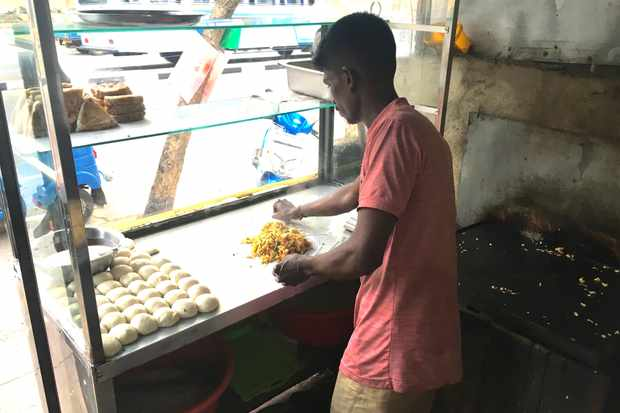 A man named Kadesh makes kottu at a street food stall in Galle