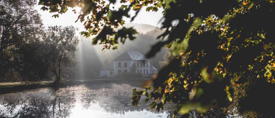 A sparkling lake is dappled with sun and has green trees covering part of the image. In the background is Le Barn