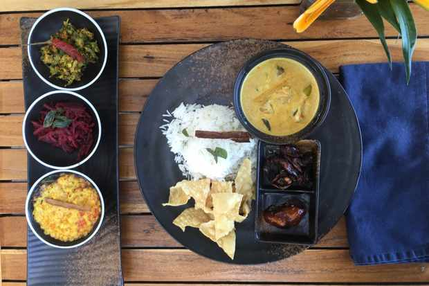 A wooden table is topped with a round slate plate. On top of the plate is a fish curry, rice and poppadums. To the side are three pots filled with sambol and colourful chutneys