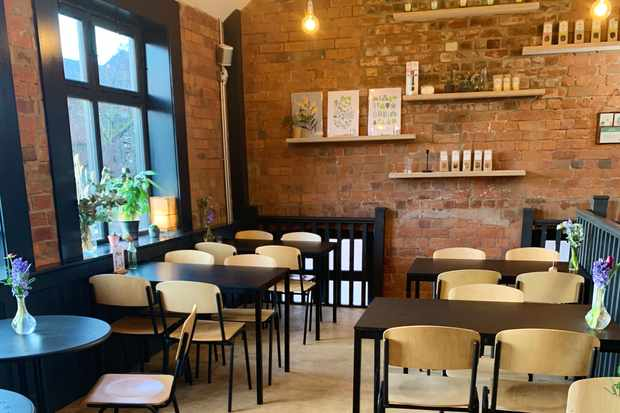 A room is filled with school-style tables and chairs. There is exposed brickwork and vases filled with flowers