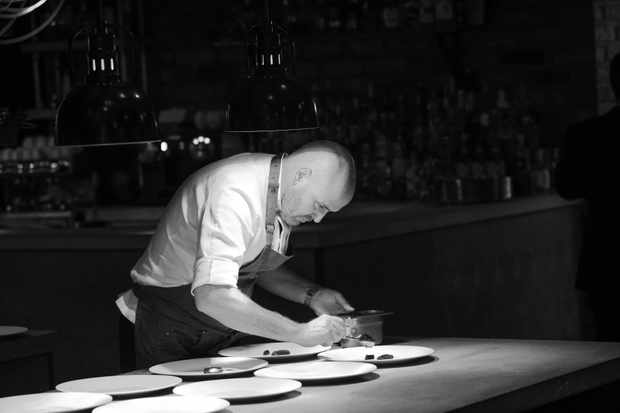 A black and white photo of chef Aiden Bryne. He is plating up food on white plates