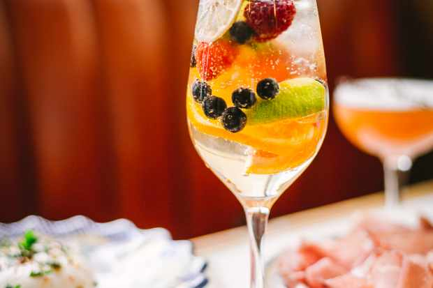 A wine glass is filled with a cocktail and filled with berries, oranges and slices of lime