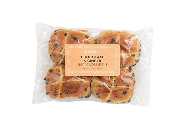 A plastic packet filled with four chocolate and ginger hot cross buns