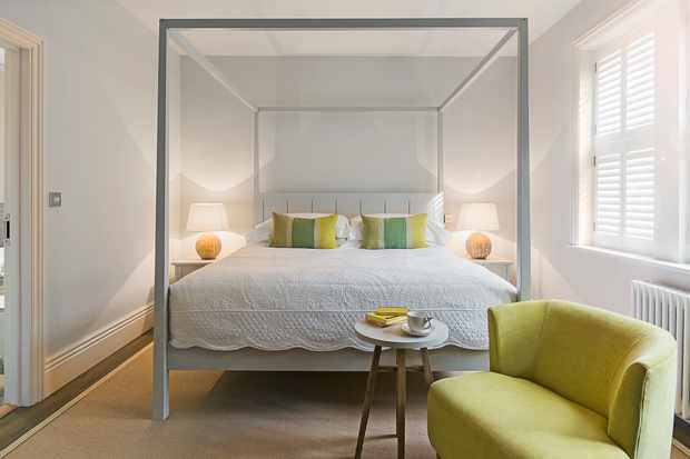 A bedroom at Brocco in Sheffield. The bedroom has white walls and a modern four poster bed. There is a lime green sofa in the edge of the image and two small side tables either side of the bed