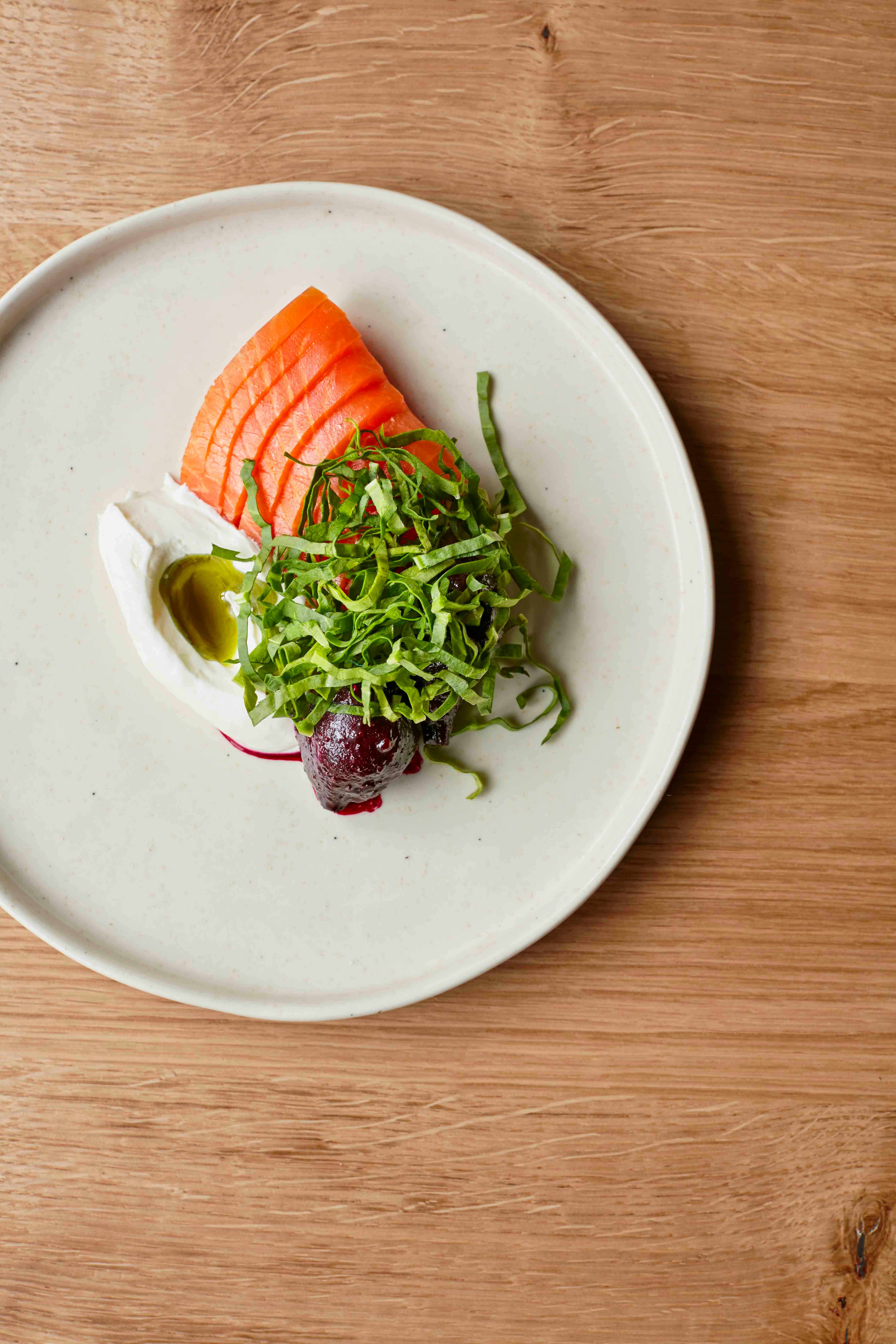 A pale greyish green plate is topped with sliced salmon and green leaves