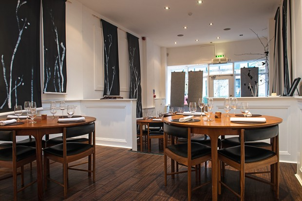 A two-level restaurant has dark wooden floors and circular tables and chairs. There are white walls with long black painting hung on them that reflect the Scottish landscape