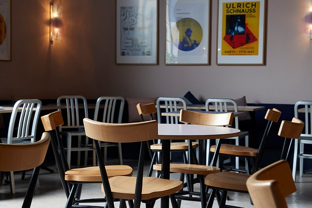 An open space has pale pink walls lined with retro prints in black frames. There are wooden tables and chairs dotted around
