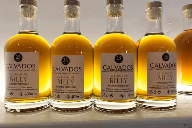 Bottles of deep-yellow-coloured calvados line a shelf