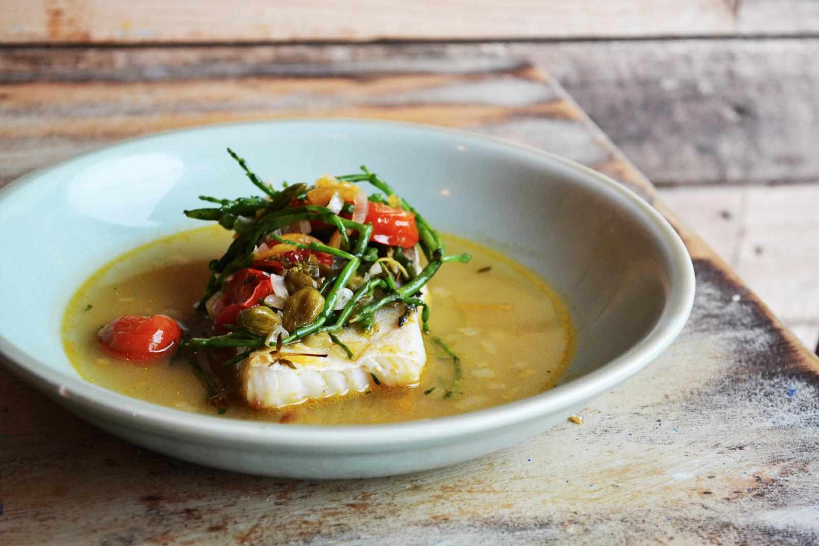 On a wooden table sits a bowl. In the bowl is a piece of hake in a yellow broth. It is topped with samphire and tomatoes