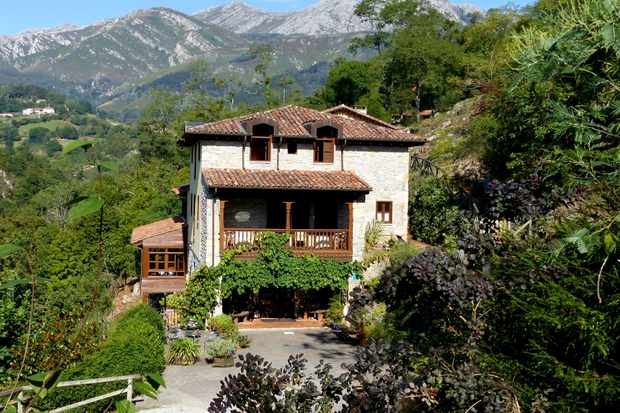 An old cream stone building with wicker roof surrounded by lush greenery and rolling hills in Asturias, Spain