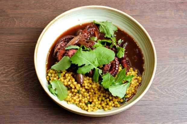 A bowl is filled with deep-red coloured slow cooked octopus and yellow grains of giant couscous.