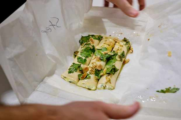 Greaseproof paper is filled with three cannelloni, each one filled with irkotta cheese and topped with a mixture of lemon zest, flaked almonds and parsley