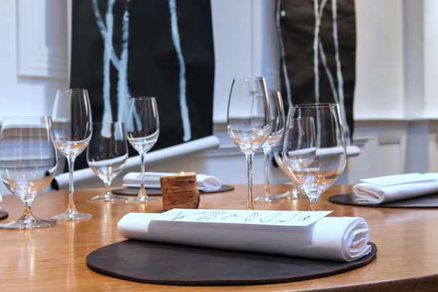 A wooden table is simply laid with wine glasses and white napkins. On the napkins sits a white paper menu which has no words, just line drawings of different ingredients