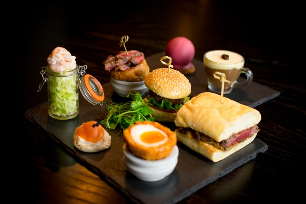 A slate topped with mini burgers, a scotch egg and small sandwiches