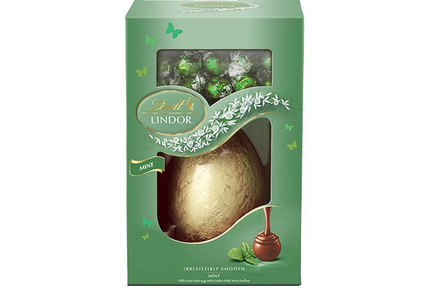 A green box is filled with an egg wrapped in gold foil and there are truffles wrapped in mint green foil at the top of the box