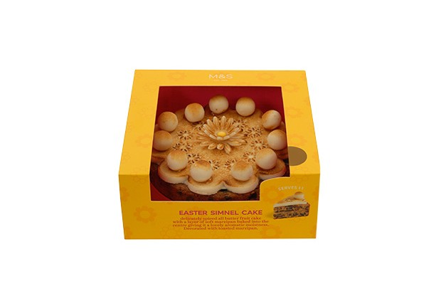 A simnel cake with marzipan balls on top in a yellow box