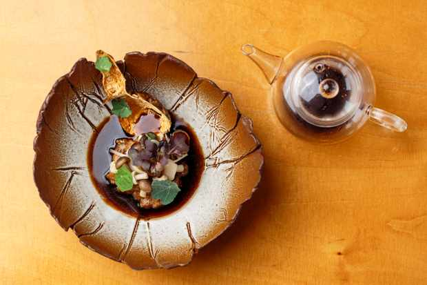 A decorative bowl is filled with a mushroom and Jerusalem artichoke risotto. There is a deep brown sauce and a teapot on the side filled with the sauce
