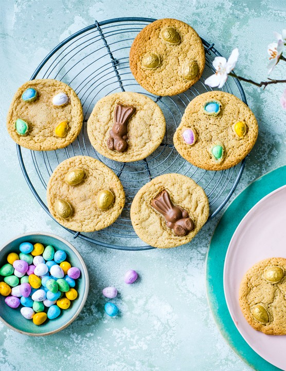 A selection of Easter cookies topped with coloured M&M eggs, Maltesers bunnies and golden eggs