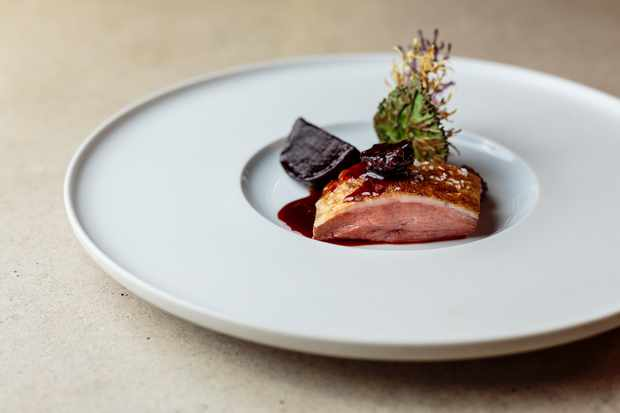 A shallow white bowl with a large rim is topped with a perfectly pink piece of duck breast. There is a deep purple beetroot puree and a chunk of beetroot