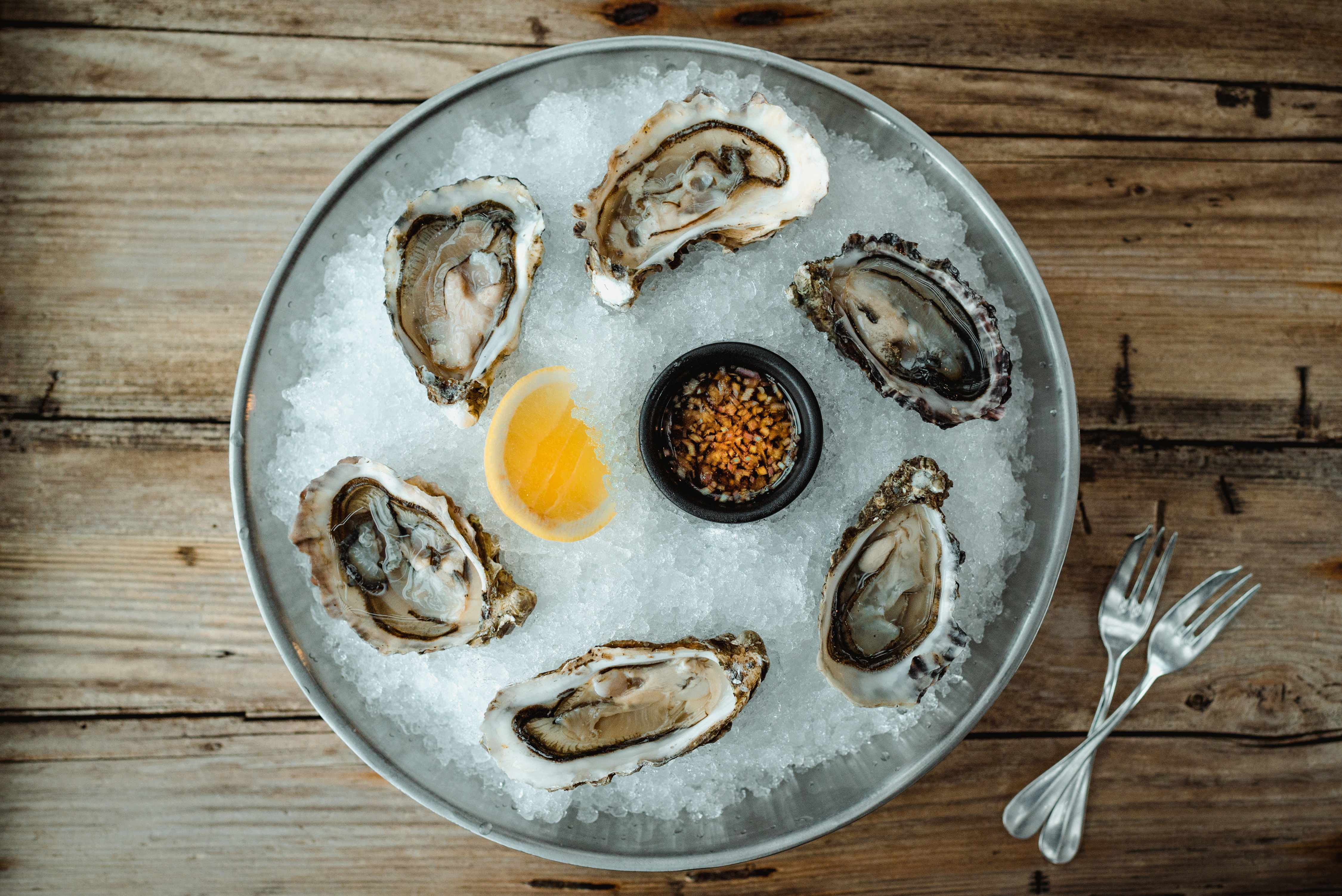 A wooden table has a platter laid on it. In the platter sits oysters in their shells on a bed of ice