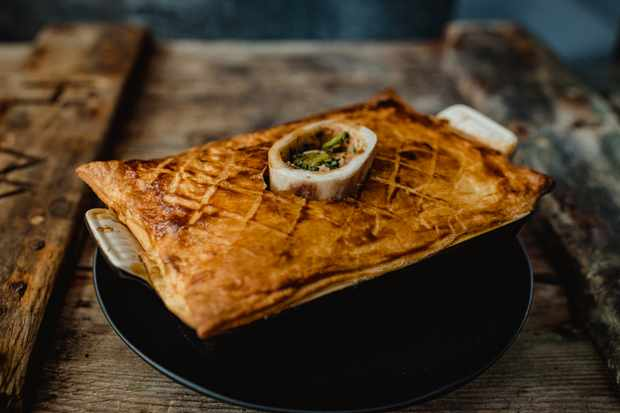 A black baking dish is filled with a steak pie. There is a golden puff pastry crust with bone marrow peeping out the top