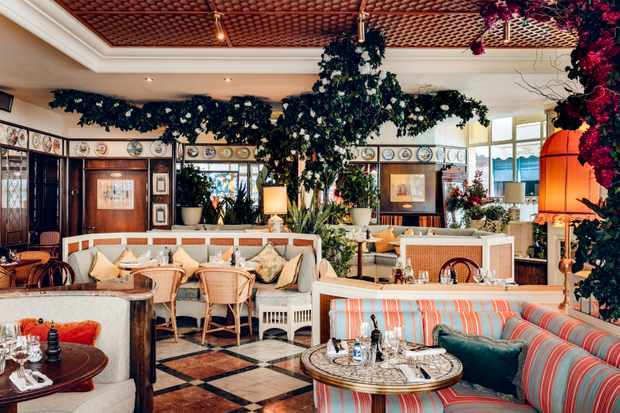 A colourful Italian-inspired dining room at Gloria restaurant. There is a tiled floor, plants dotted around. Marble tables and colourful antique ceramics