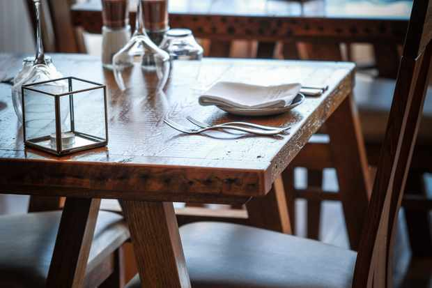 Wooden tables are simply laid with wine glasses, white napkins and a candle holder