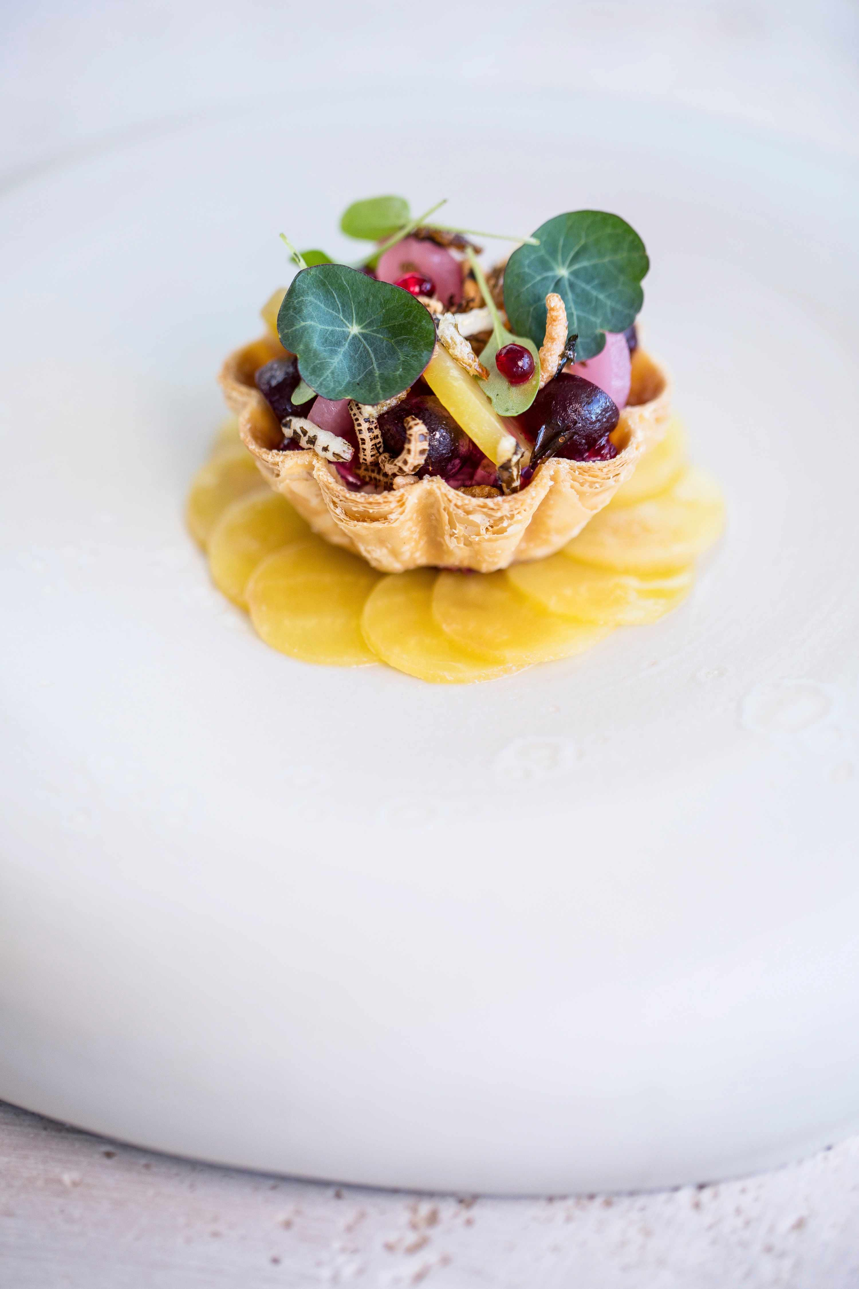 A delicate pastry tart with pretty crimped sides sits on a bed of thinly sliced yellow fruit