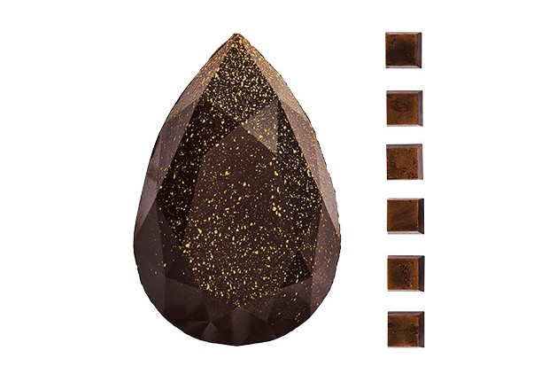 A geometric shaped dark chocolate Easter egg with six truffles displayed to the right hand side