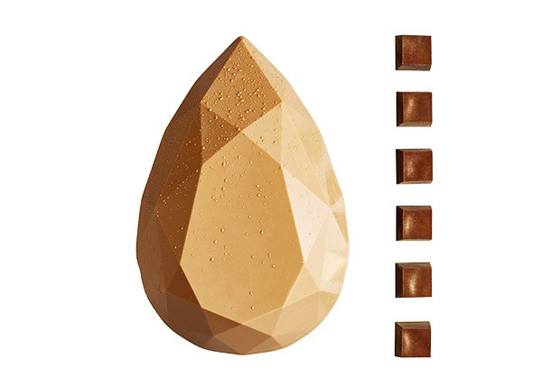 A geometric shaped white chocolate Easter egg with six truffles displayed to the right hand side