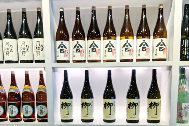 White shelves in the background of the photo are lined with bottles of sake. In the front of the photo is a tray filled with dinky glasses, each filled with sake