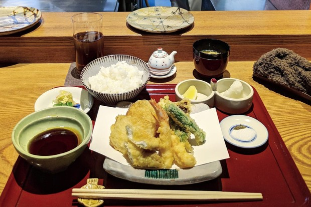 A red wooden tray is topped with dainty pots. One is filled with a dashi broth, another is filled with rice and a plate at the front it topped with crisp tempura