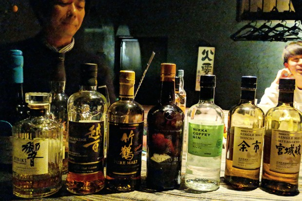 A wooden bar is lined with glass bottles of Japanese spirits. There is a man sat in the background