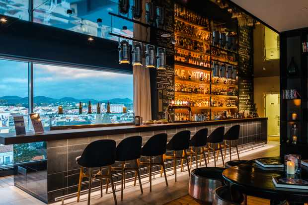 A striking bar on the Azor hotel rooftop. There is a wall lined with spirits and stools at a bar that lookout over the coast