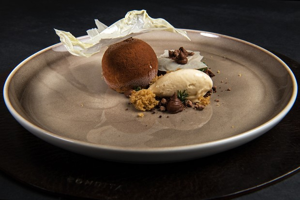 A large plate is set against a black backdrop. On the plate is a dark coffee sphere with chocolate soil, a creamy mocha butter and a delicate milk crisp